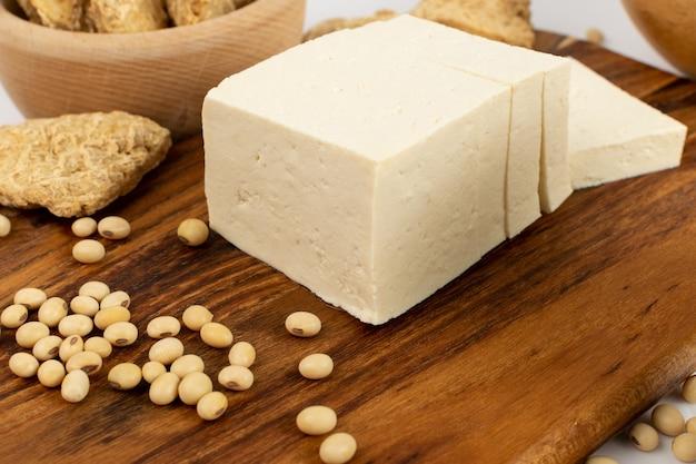 Сыр фтеш тофу или веганский сыр на деревенском виде сбоку стола. нарезанный соевый творог, соевый белок или tsp Premium Фотографии