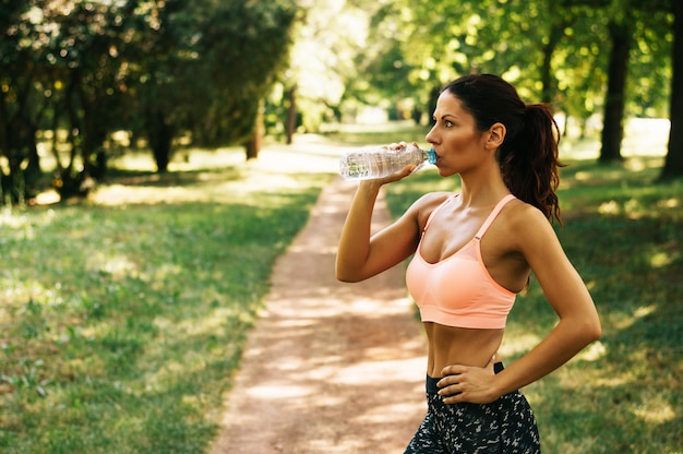 Ftness athlete woman drinking water after work out exercising outdoor. Premium Photo