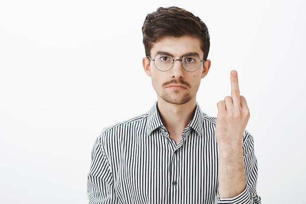 ファックオフ、私はあなたの奴隷ではありません。灰色の壁をあざけるのにうんざりしていて、中指と穏やかな表情を見つめている、剛毛と口ひげを持つ腹が立つ深刻な成人男性 無料写真