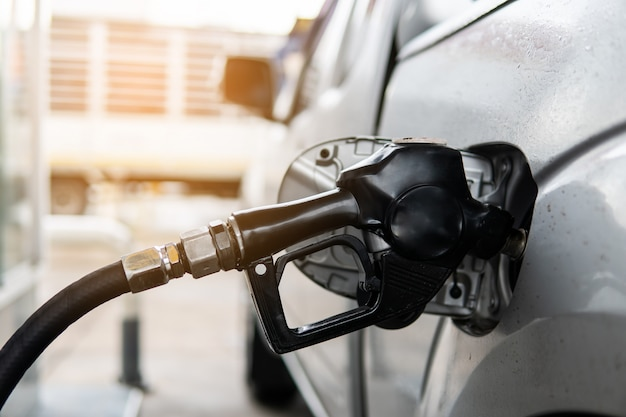 Fuel nozzle to refill fuel in car at gas station. Premium Photo