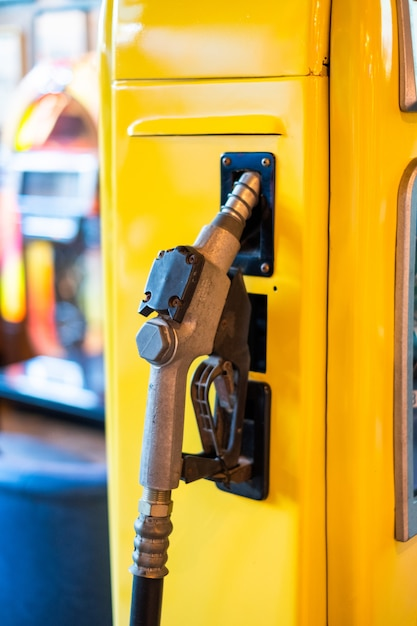 Fuel nozzle on yellow petrol pump Premium Photo