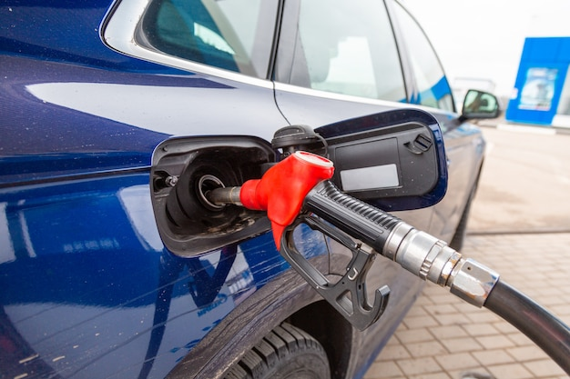 Fuelling gun inserted into the tank of blue car Premium Photo