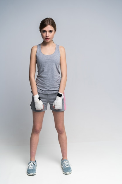 Full body of beautiful boxer girl wearing sportive clothing and gloves practicing in the studio over gray Premium Photo