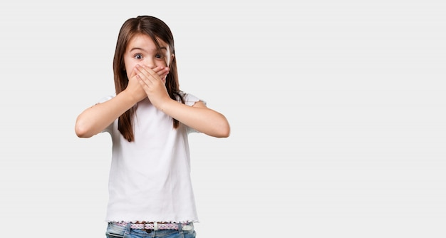 Full body little girl covering mouth, symbol of silence and repression, trying not to say anything Premium Photo