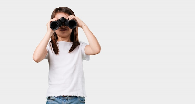 Full body little girl surprised and amazed, looking with binoculars in the distance something interesting, concept of future opportunity Premium Photo