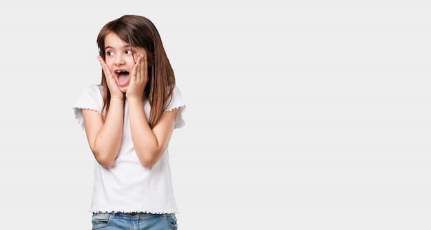 Full body little girl surprised and shocked, looking with wide eyes, excited by an offer or by a new job, win concept Premium Photo