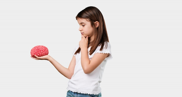 Full body little girl thinking and deducting, looking at a brain trying to understand it Premium Photo