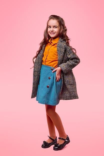 ピンクの背景に子供のための季節のファッションを表すカジュアルな服とスタイリッシュな市松模様のコートで愛らしい笑顔の女子高生の全身 Premium写真