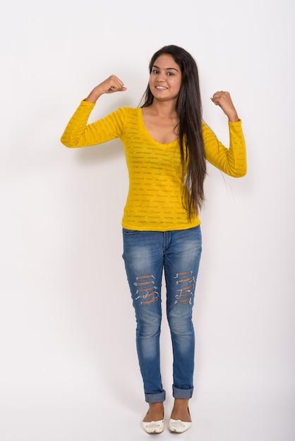 Снимок всего тела молодой счастливой женщины, улыбающейся и стоящей, сгибая обе руки Premium Фотографии