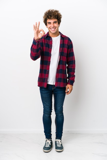 Full body young caucasian man isolated cheerful and confident showing ok gesture. Premium Photo