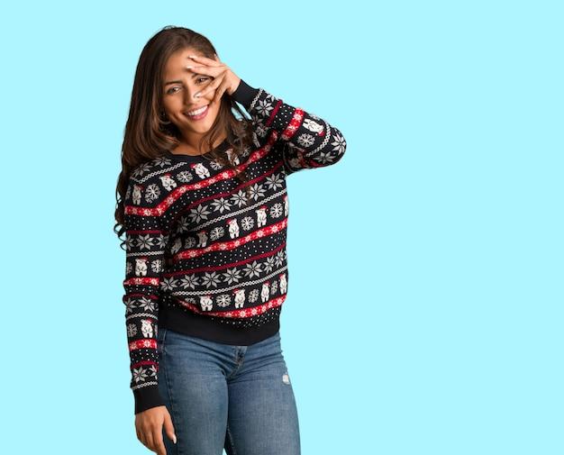 全身の若い女性は、同時に恥ずかしいと笑っているクリスマスのジャージーを着て Premium写真