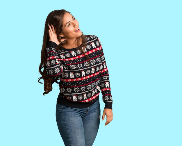 Full body young woman wearing a christmas jersey try to listening a gossip Premium Photo