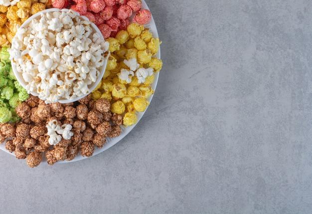 Ciotola piena di popcorn con un mucchio sparso su un pezzo di stoffa su marmo. Foto Gratuite