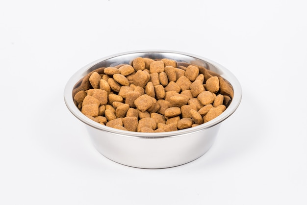 A full cup with pieces of dry pet food isolated. metal food bowl for cat or dog Premium Photo