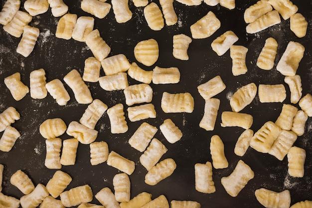 Full frame di gnocchi di pasta fatta in casa non cotti sul piano di lavoro della cucina Foto Gratuite