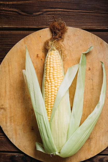 Full grown corn with leaves on a cutting board Free Photo