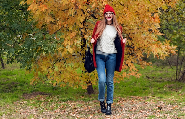 Full height autumn fashion image of pretty nice woman in red stylish coat and knitted hat, red lips posing on yellow park. Free Photo