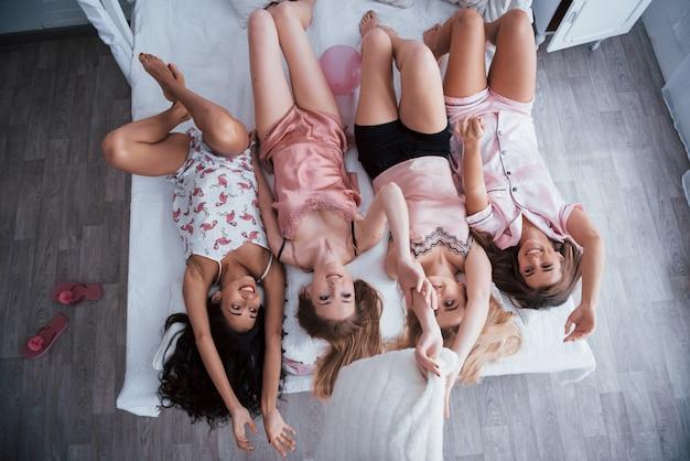 全高。ナイトウェアのベッドに横たわっている魅力的な女の子の逆の肖像。上面図 無料写真