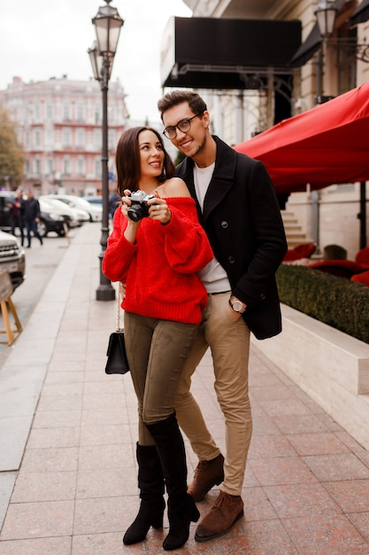 Full height outdoor image of fashionable elegant couple in love walking on the street during date or holidays. brunette woman in red sweater making photos by camera. Free Photo