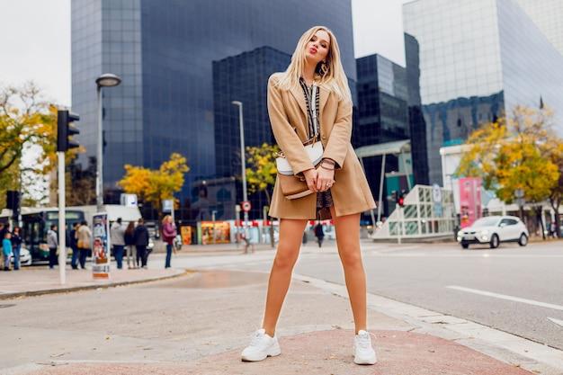 都市通りでポーズかなりブロンドの女性の完全な高さの肖像画。ベージュのコートと白いスニーカーを着用しています。トレンディなアクセサリー。通りを歩いて屈託のない女性。 無料写真