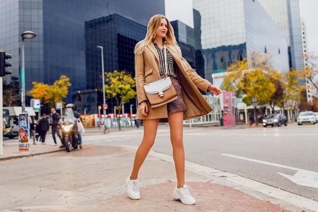 都市でポーズかなりブロンドの女性の完全な高さの肖像画。ベージュのコートと白いスニーカーを着用しています。トレンディなアクセサリー。通りを歩いて屈託のない女性。 無料写真
