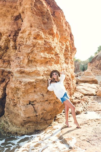 Foto a figura intera di bella ragazza bionda con i capelli lunghi in posa per la fotocamera sulla spiaggia su sfondo di roccia. Foto Gratuite