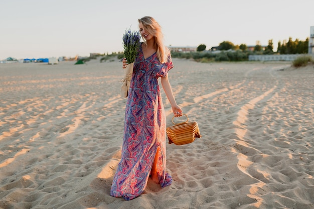 Полное изображение красивой белокурой женщины с букетом лаванды, идущей на пляже. цвета заката. Бесплатные Фотографии