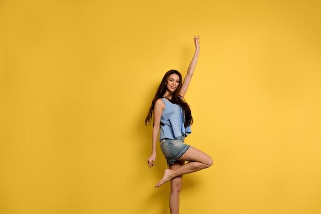 Полное фото счастливой возбужденной женщины в синей футболке и джинсовой юбке, прыгающей с улыбкой Бесплатные Фотографии