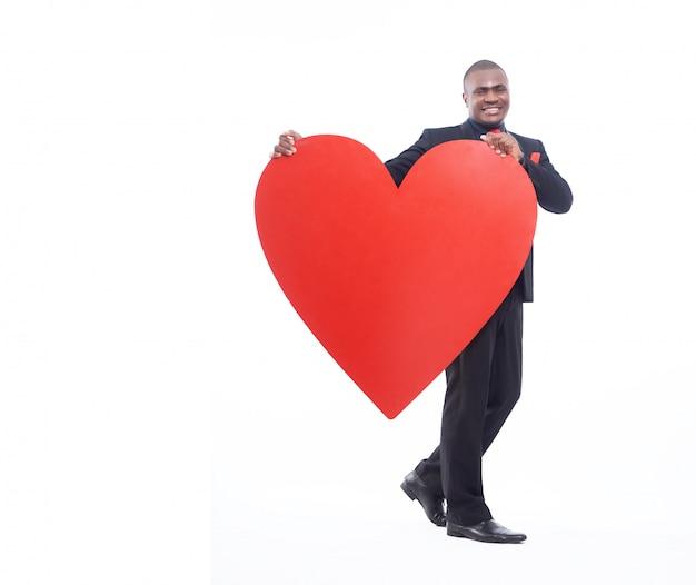 大きな赤いハートを保持している若いアフリカ人の完全な長さの肖像画 無料写真