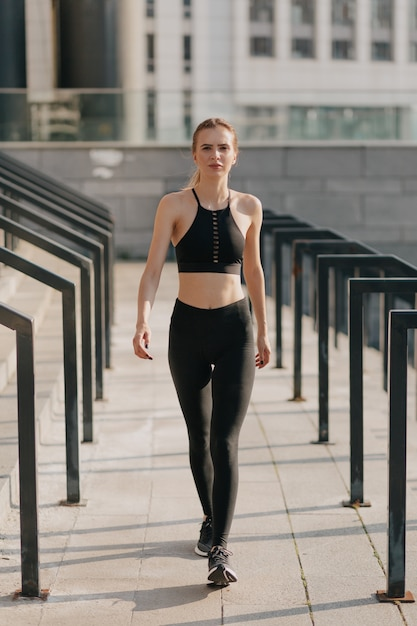 Full-lenght portrait of woman wearing sport suit and walking Free Photo