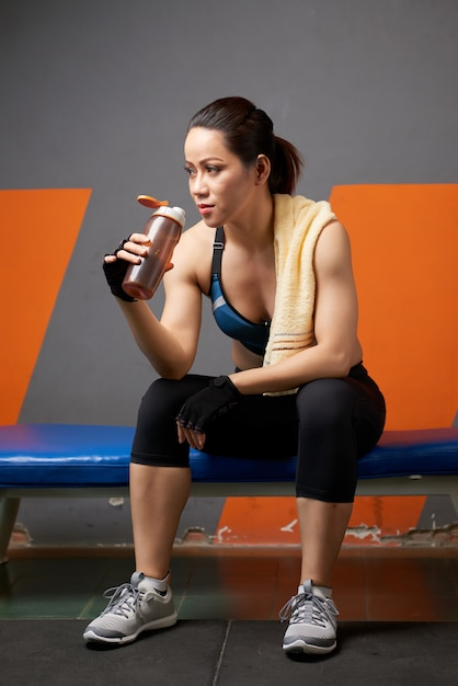 Full length of athlete sipping water from the fitness bottle exhausted after the workout Free Photo