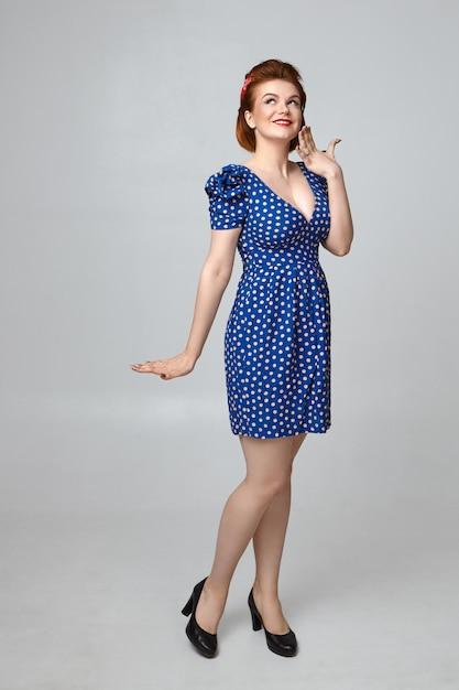 Bella ragazza pin up europea a figura intera in elegante abito blu con taglio a collo basso che ha un aspetto timido, sorridendo ampiamente mentre flirta con qualcuno. espressioni facciali umane e corpo Foto Gratuite