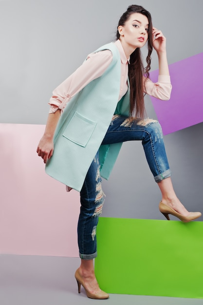 Full length of beautiful girl, with green blank advertising board , over gray background and pink and violet banner Premium Photo