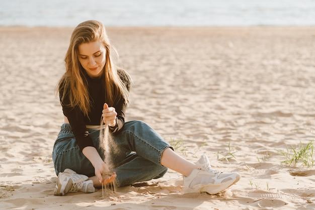 完全な長さの美しい女性の夕暮れ時のビーチに座って砂を注ぐ。スローライフ Premium写真