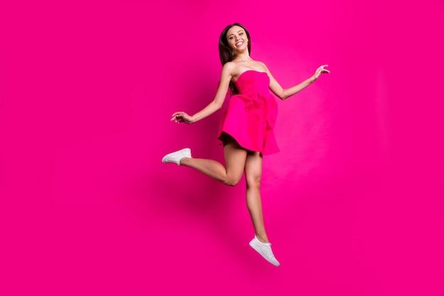 Вид ее в полный рост, она красивая привлекательная, привлекательная, веселая, длинноволосая девушка, летящая, развлекаясь, наслаждаясь свободным временем, изолированным на ярком ярком сиянии яркого розового цвета фуксии. Premium Фотографии