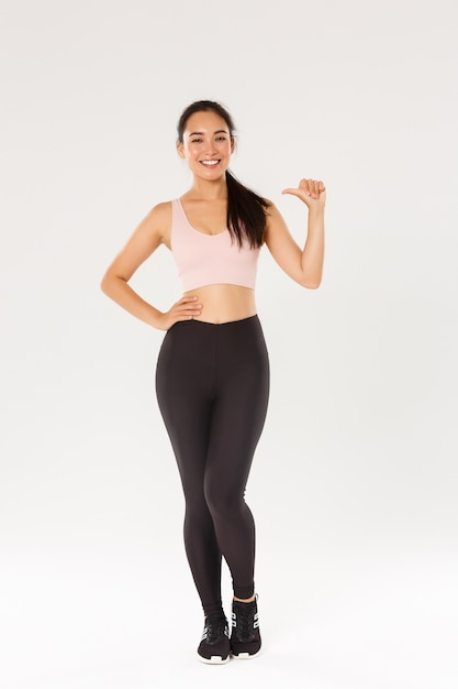 Full length of confident smiling asian female athelte in sportsbra and leggigns, fitness girl pointing at herself, lead active and healthy lifestyle, being professional, standing white background. Free Photo