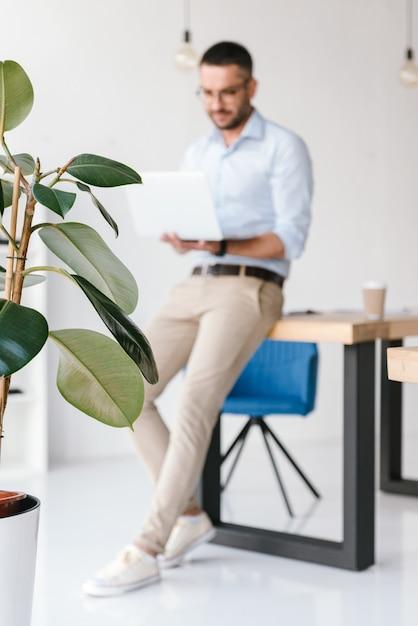 사무실에서 테이블에 앉아 은색 노트북에서 작업하는 흰색 셔츠를 입고 전체 길이 Defocused 우아한 남자 프리미엄 사진