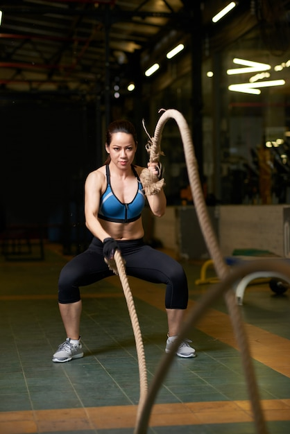 Full length of fit girl doing crossfit exercise Free Photo