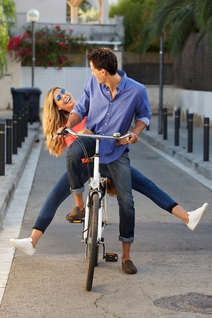 Full length fun couple riding bicycle together on path Premium Photo