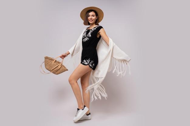 Полная длина рада женщина с короткой прической в стильном летнем наряде бохо. соломенная шляпа и сумка. Бесплатные Фотографии