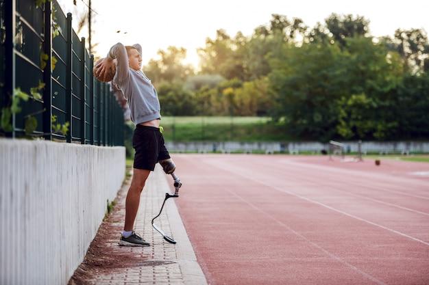 전체 길이 잘 생긴 백인 스포티 한 장애인 남자 스포츠웨어와 농구 공을 던지는 동안 울타리에 기대어 인공 다리. 프리미엄 사진