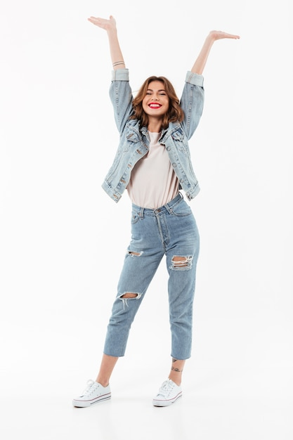 Full length happy woman in denim clothes having fun   over white wall Free Photo