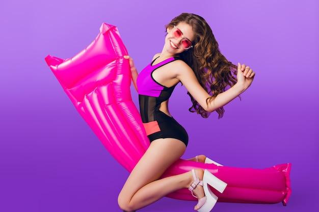 スタジオで紫色の背景にピンクのサングラスで長い巻き毛を持つ魅力的な女の子の全身水平写真。彼女は水着を着て、ピンクのエアマットレスを楽しんでいます。 無料写真
