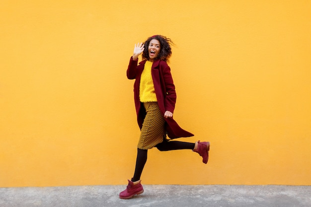 Full length image of excited woman jumping with happy face expression on yellow. Free Photo
