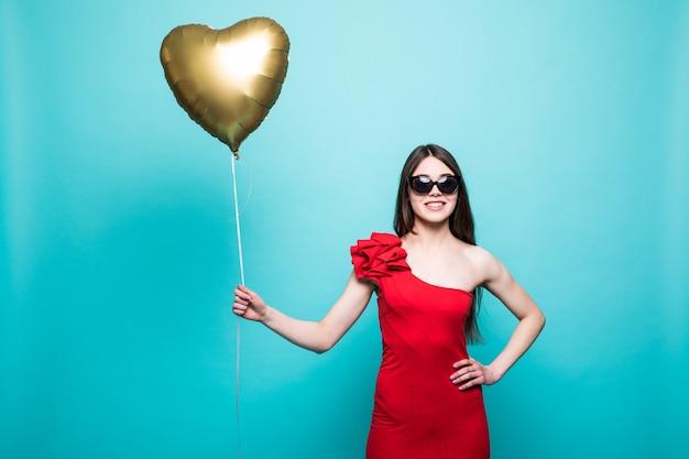 Immagine a figura intera di splendida donna in abito rosso fantasia in posa con palloncino a forma di cuore, isolato sopra la parete verde Foto Gratuite