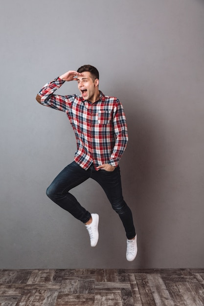 Full length image of happy man in shirt and jeans jimping and looking away with arm in pocket Free Photo