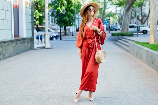 ヨーロッパの都市で休暇を過ごすファッショナブルな女性の全身像。驚くほどトレンディなサンゴの自由奔放に生きるドレス、かかと、ストローバッグを着ています。 無料写真
