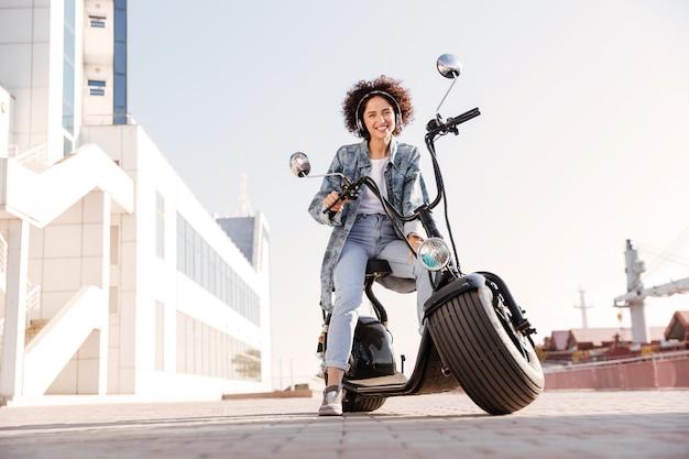Полнометражное изображение улыбающейся кудрявой женщины, сидящей на мотоцикле Бесплатные Фотографии