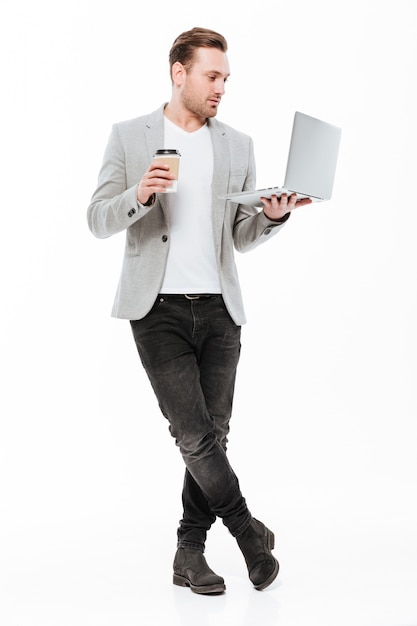 Full-length image of young entrepreneur in jacket standing with silver laptop and takeaway coffee in hands, isolated over white wall Free Photo
