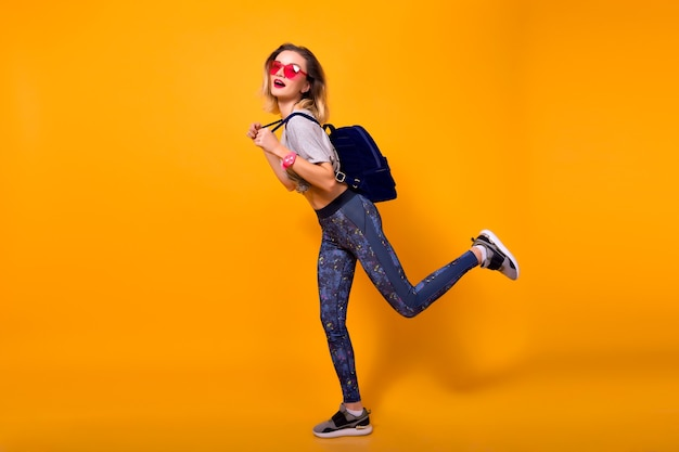 Full-length indoor portrait of girl wearing leggings, running on yellow background. pretty slim female model in sneakers with backpack fooling around in studio. Free Photo